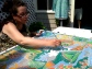 Artist Adriana Mederos putting the final touches on her hand-painted bandana