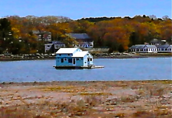 photo of little blue houseboat floating in river near Gloucester MA